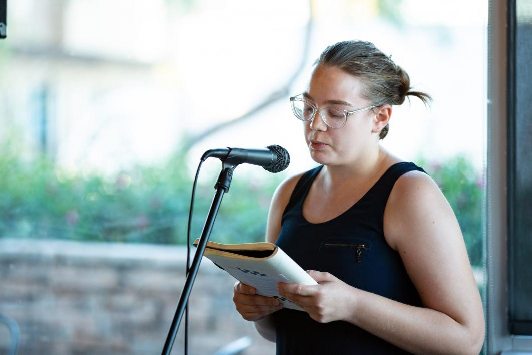 student reading poetry into microphone