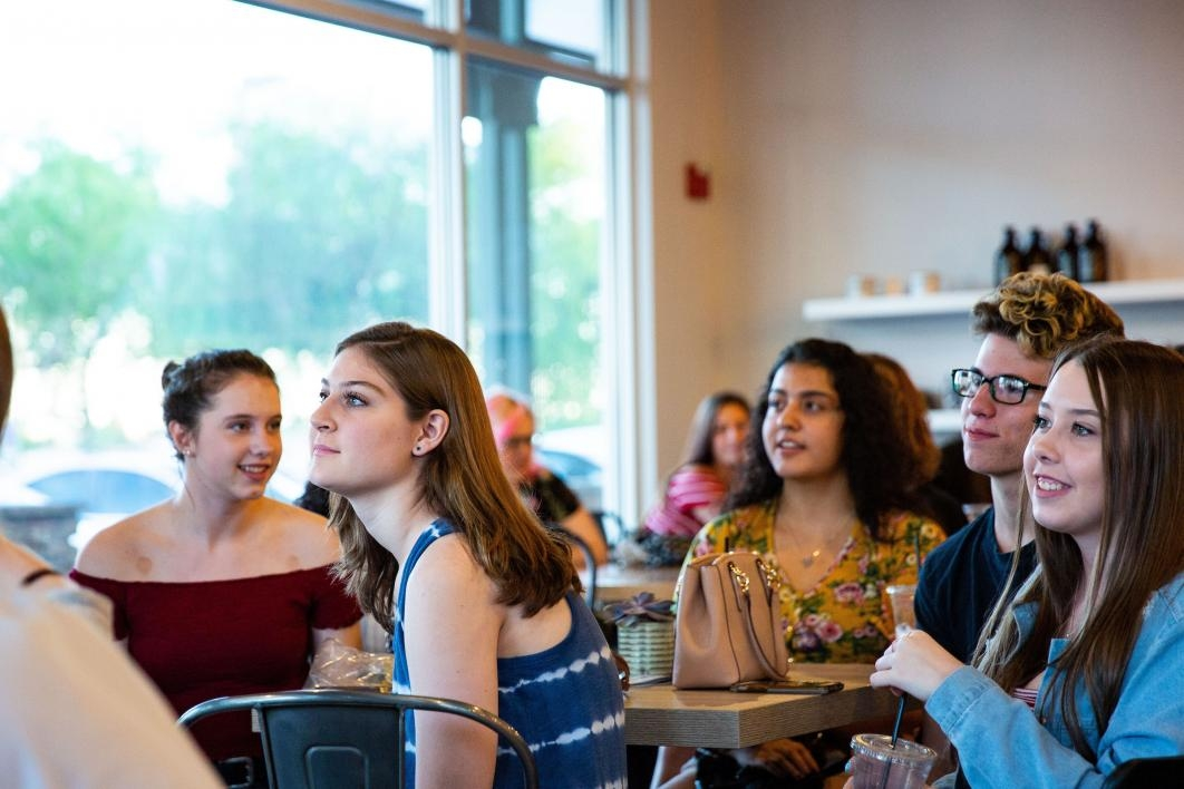 students at coffee shop listening to poetry