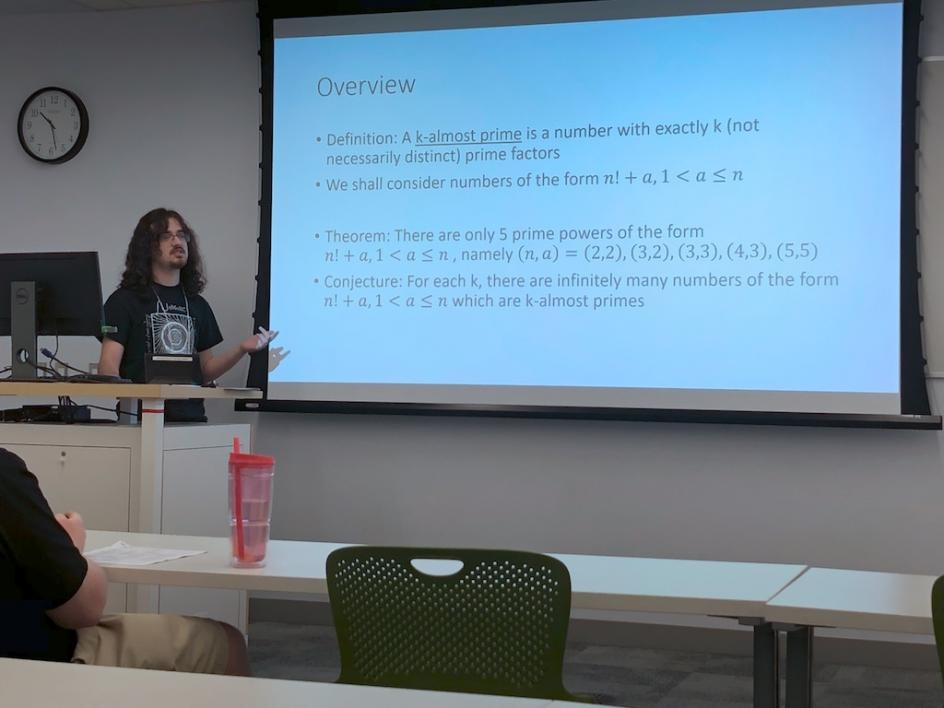 Liam Lawson presented a research talk titled Almost-Primes Near Factorials