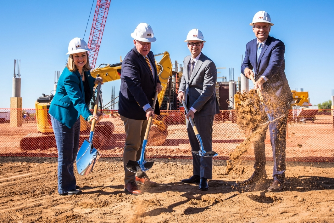 Four people turn over shovels of dirt at a ground breaking for the ASU Health Futures Center