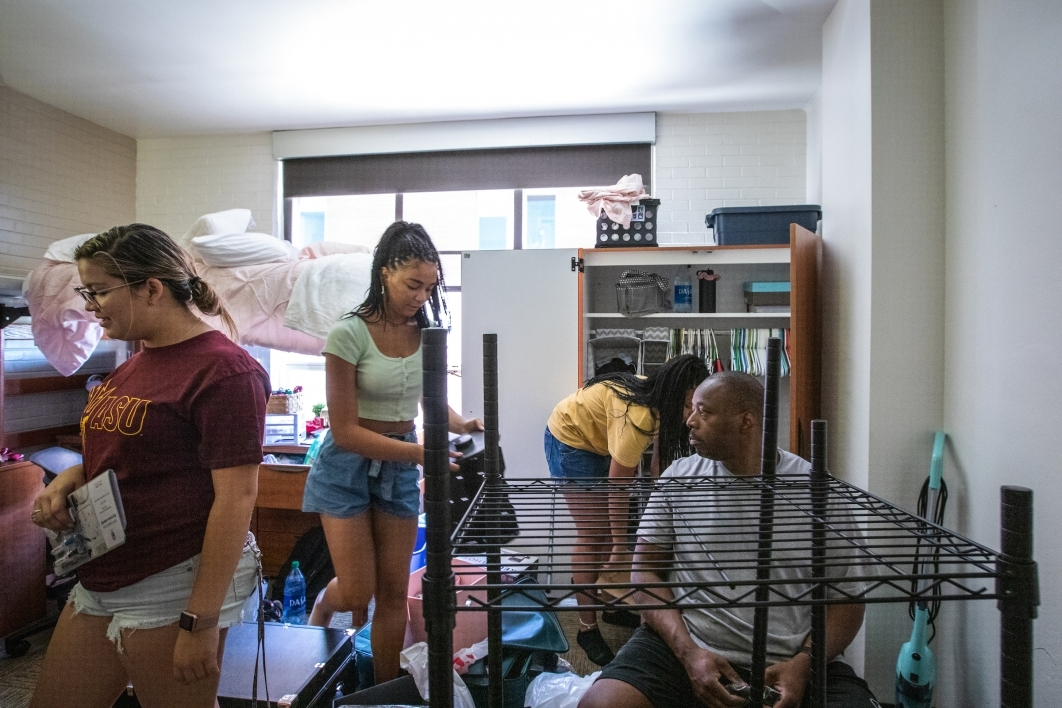 family assembling furniture in a dorm