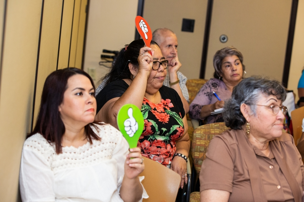 women holding up red and green paddles