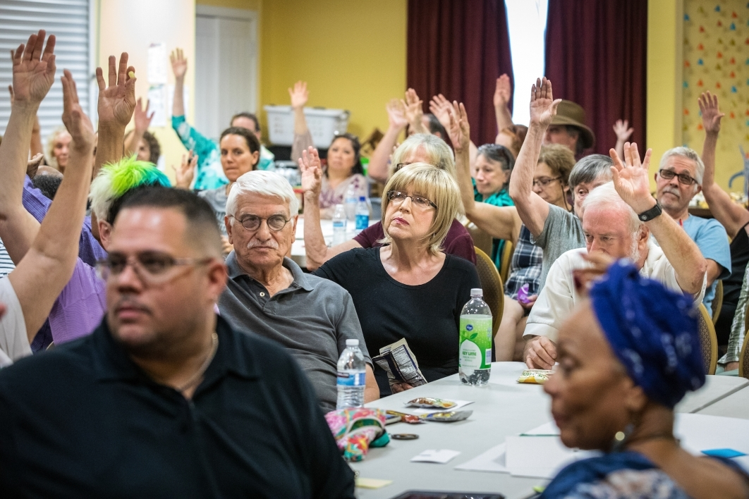 People raising their hands at a seminar