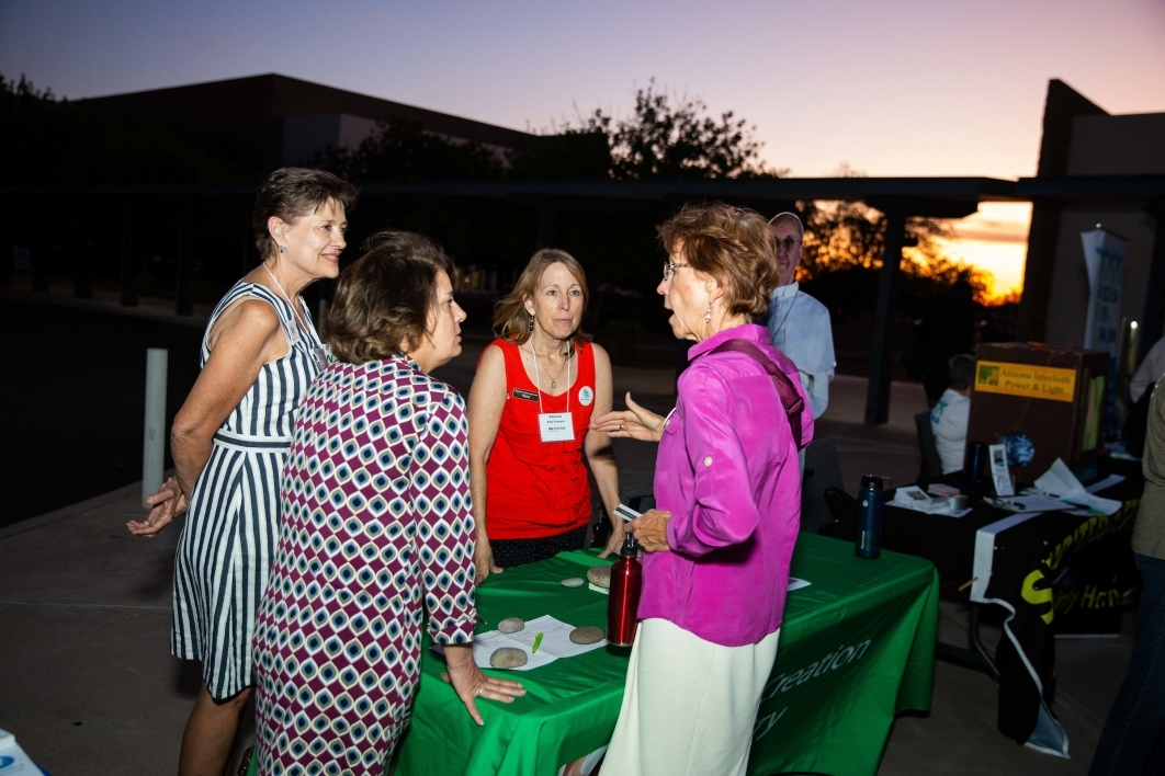 A Franciscan Renewal Center representative speaks to women at an outdoor table