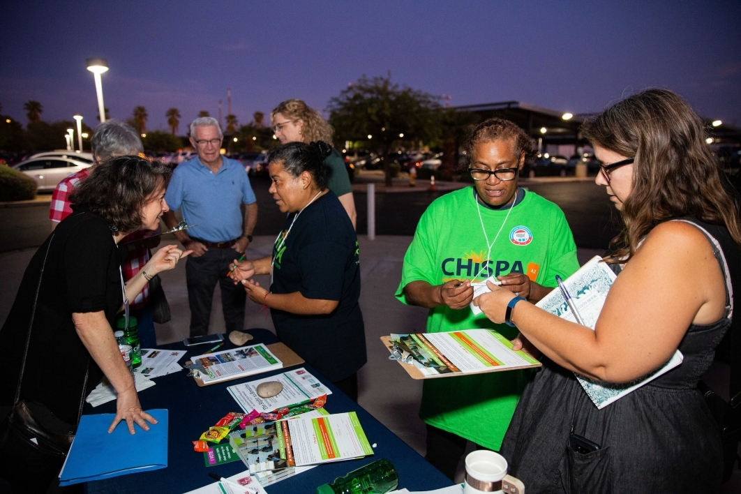 A CHISPA AZ representative speaks to visitors at an outdoor table