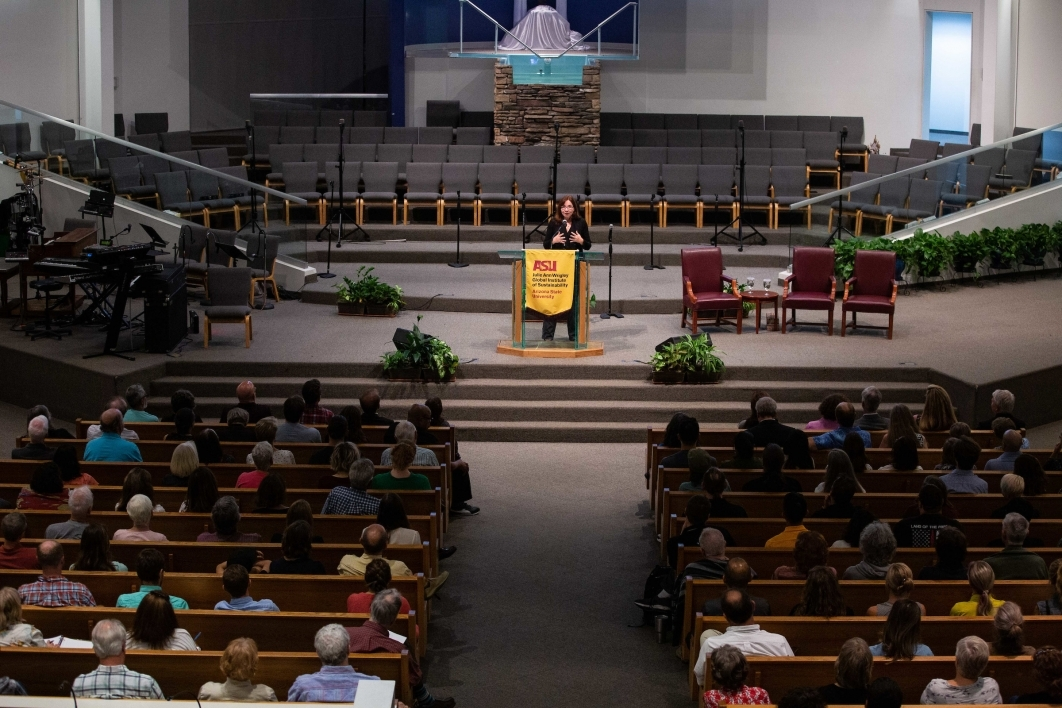 Climate scientist Katharine Hayhoe speaks from the front of a church