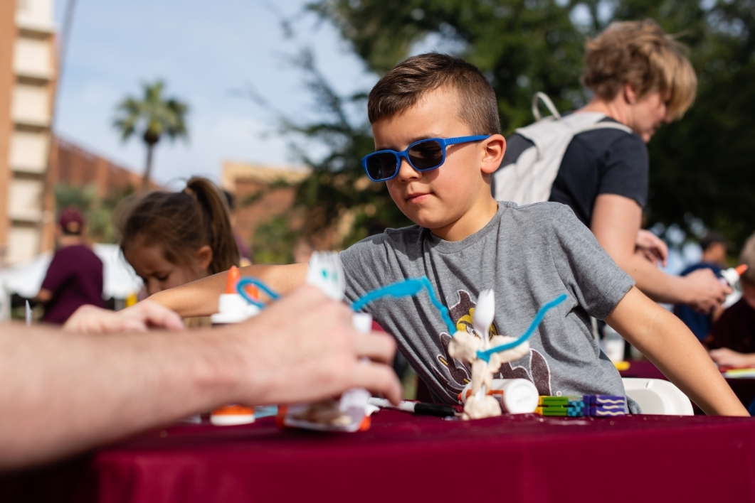 child in sunglasses makes a craft at homecoming block party