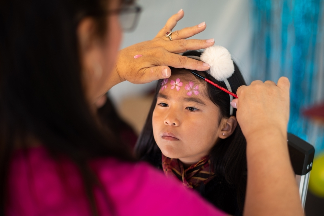 young girl gets her face painted with flowers