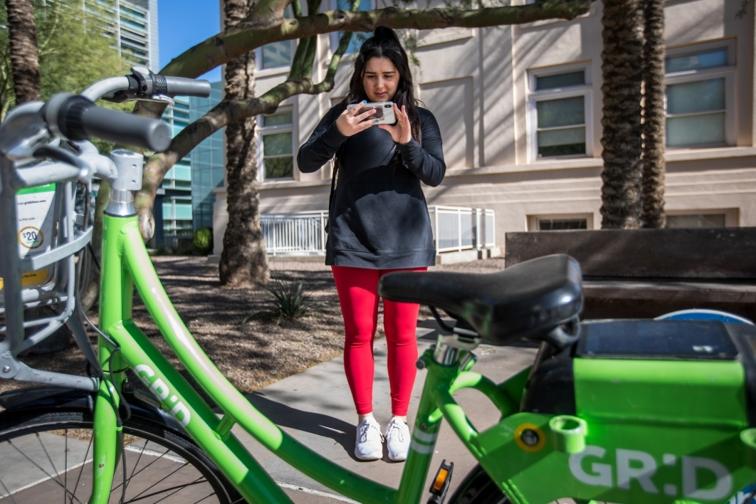 woman taking a photo of a ride-share bike with her smartphone