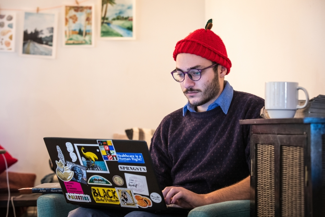 man wearing red hat sitting down and typing on a laptop in a coffee shop