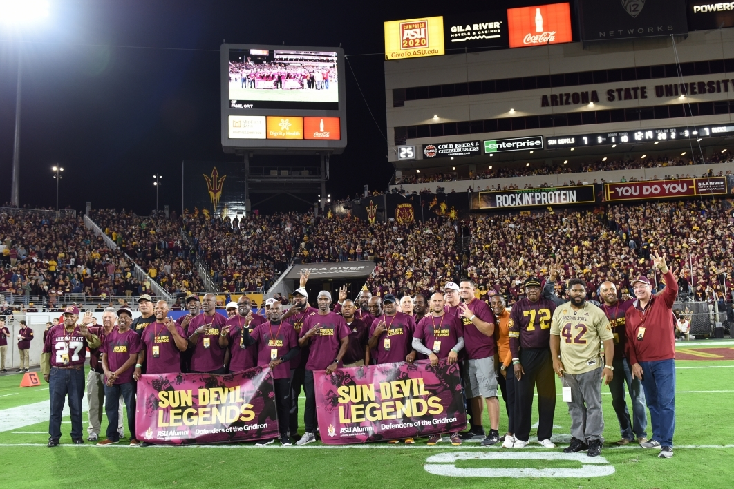 ASU football alumni gather on the field of the 2019 Homecoming game