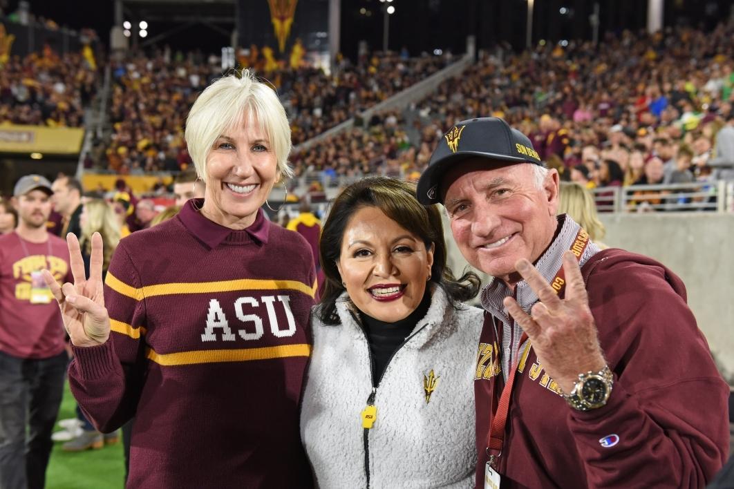 Three alumni stand on the ASU football field