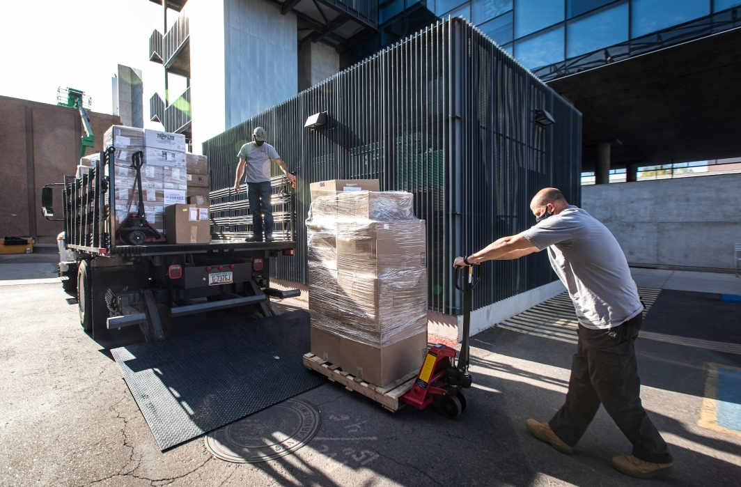 Men unload pallets of boxes of computer equipment from a truck
