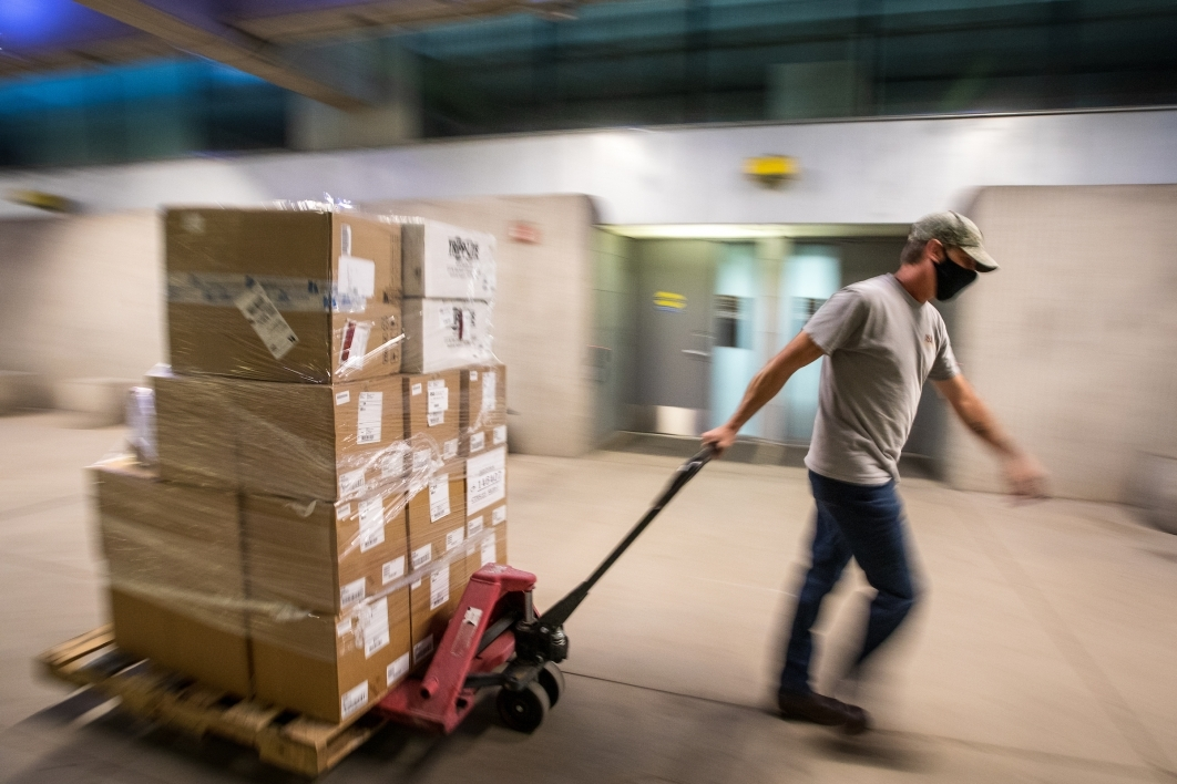 A man moves a pallet of boxes of computer equipment