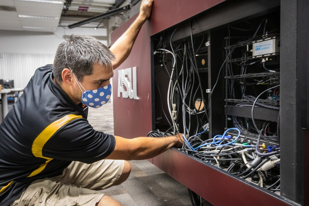 A man looks through an AV cabinet full of cables
