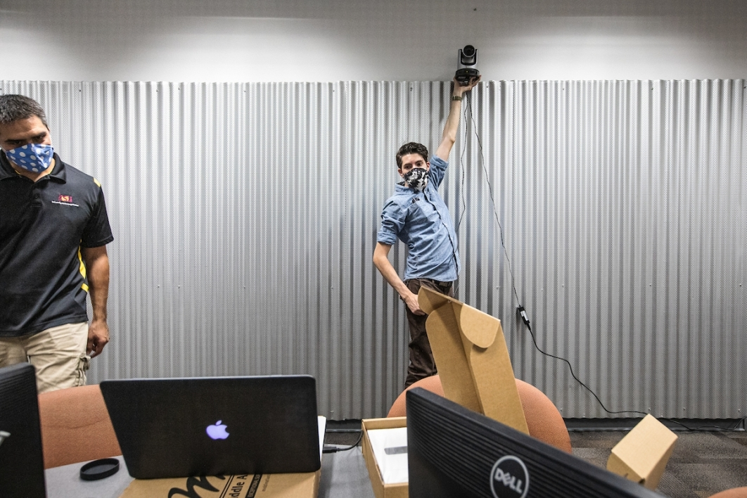 Men test out a computer camera mount on a classroom wall