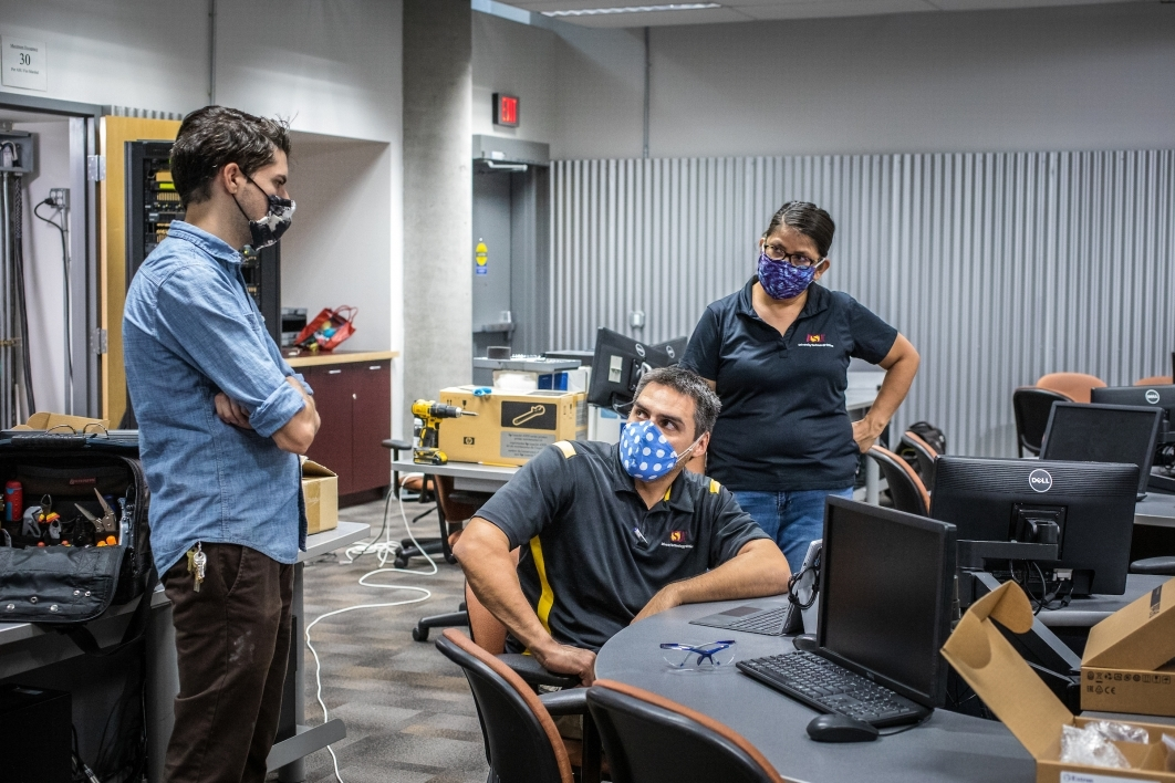 Two men and a woman discuss an AV classroom setup while wearing masks