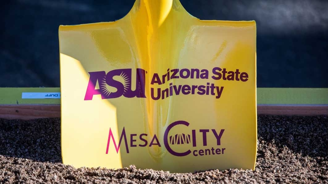 A yellow shovel in dirt with wording about ASU and the Mesa City Center in maroon