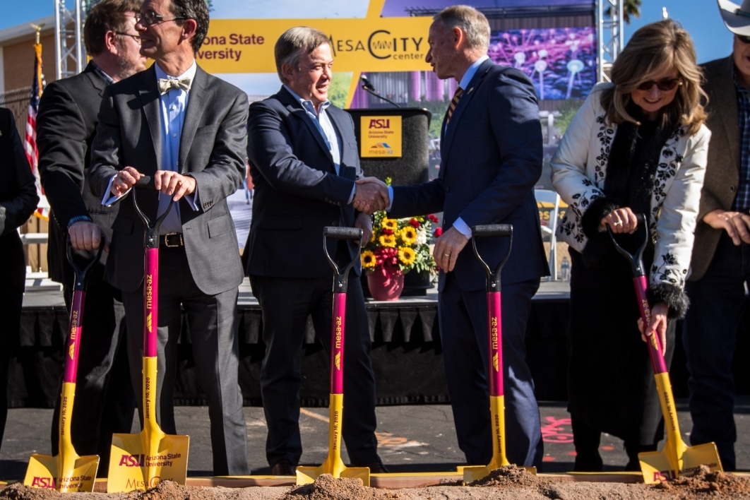 two men shaking hands behind row of shovels