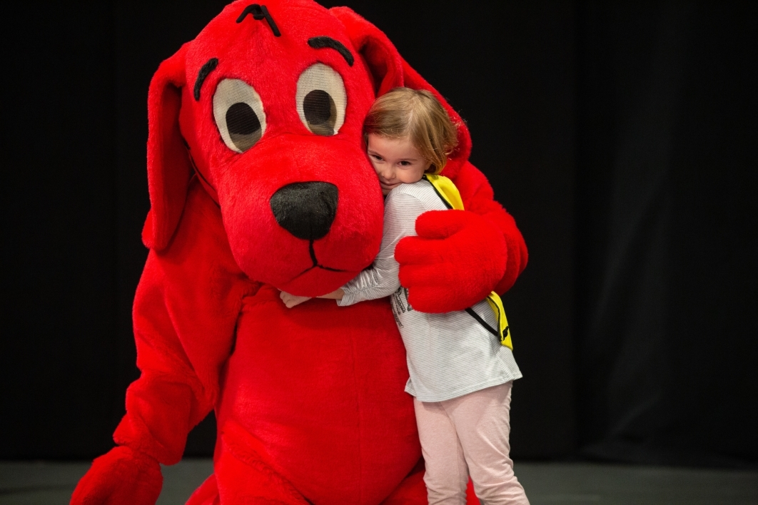 little girl hugs a Clifford the big red dog character