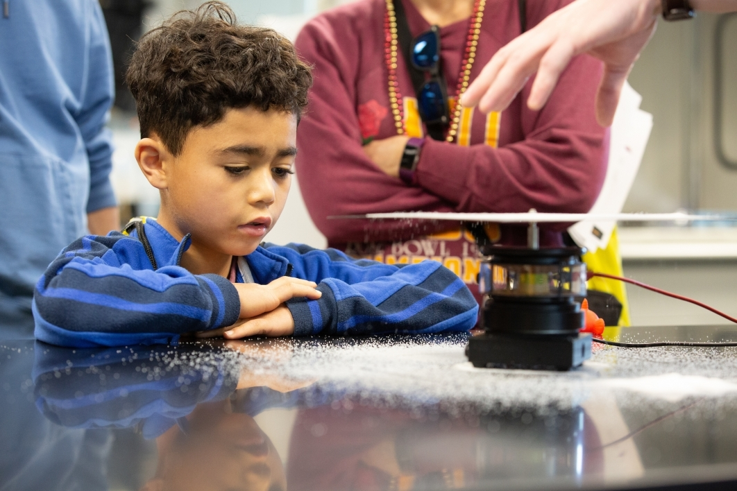 young boy watches a science experiment