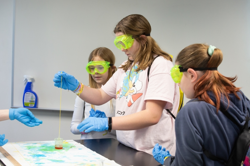 students wearing goggles and gloves mix solutions to make nylon