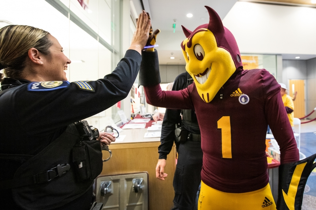 Sparky high-fiving officer
