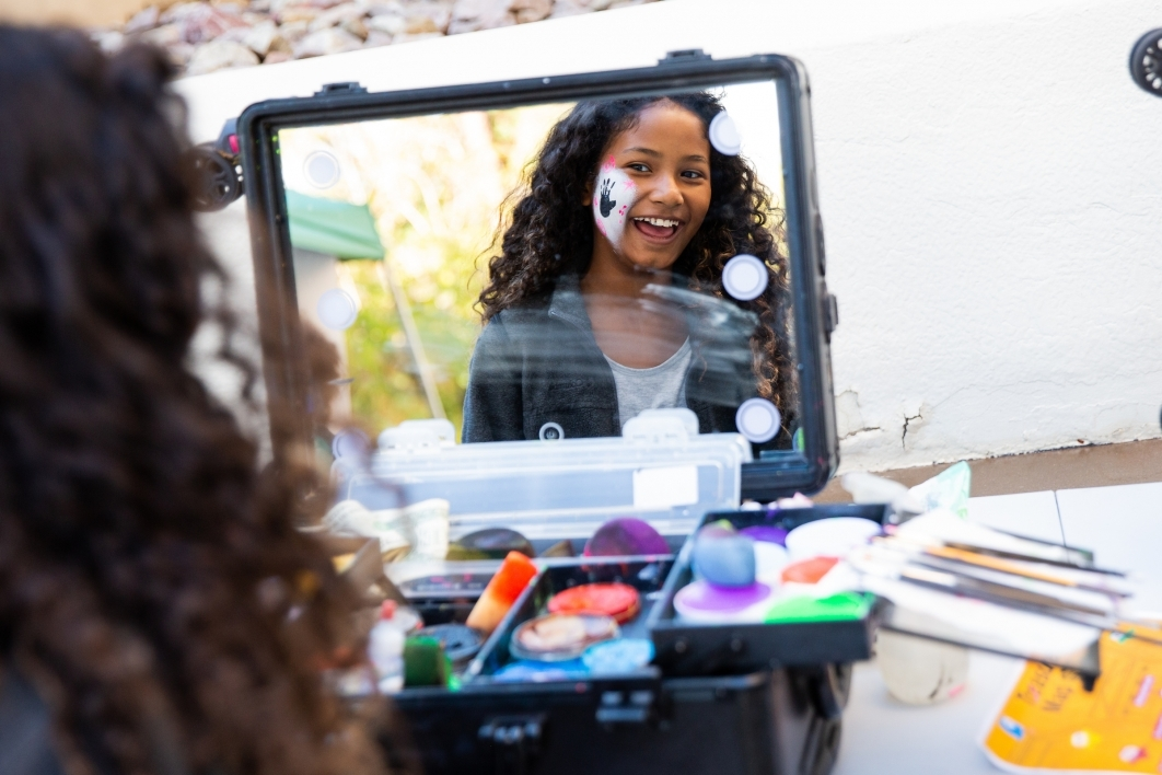 girl looking at herself in mirror with face paint