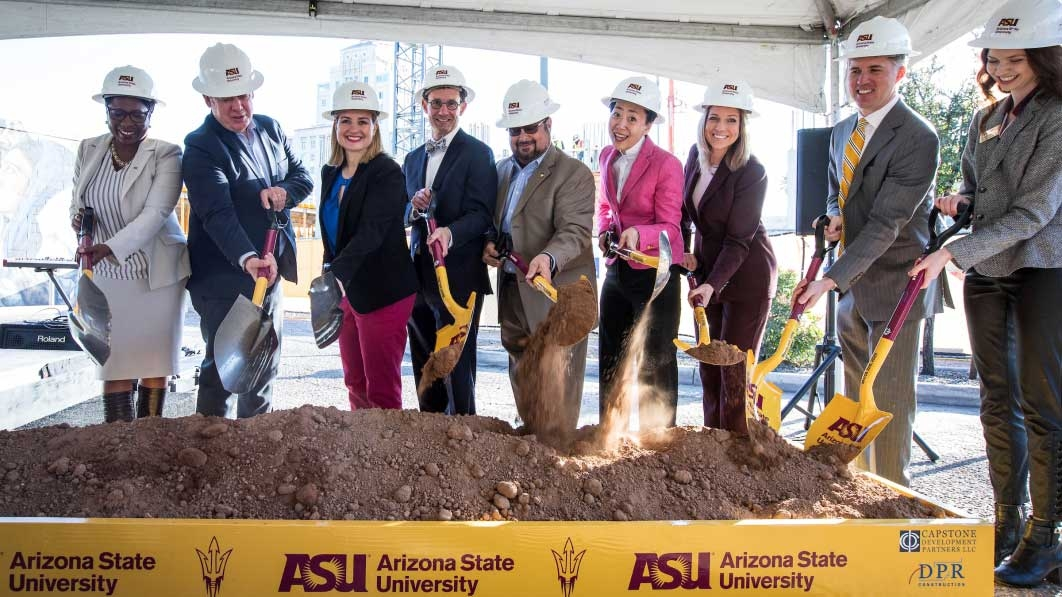 A line of people in suits and hard hats turn ceremonial dirt with shovels at a groundbreaking