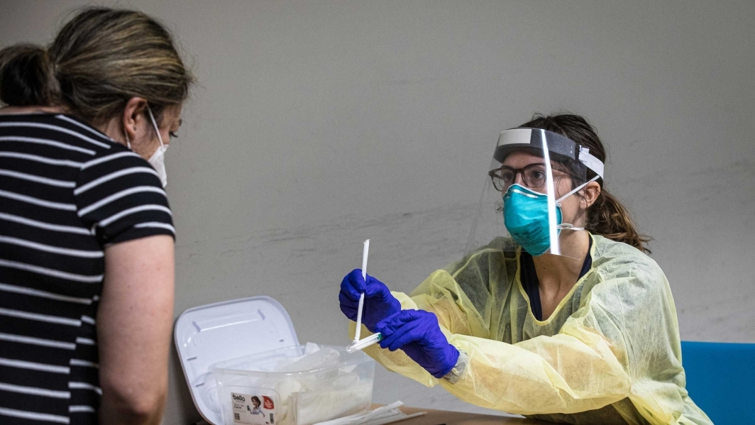 A woman in PPE hands a COVID test kit to a woman wearing a mask