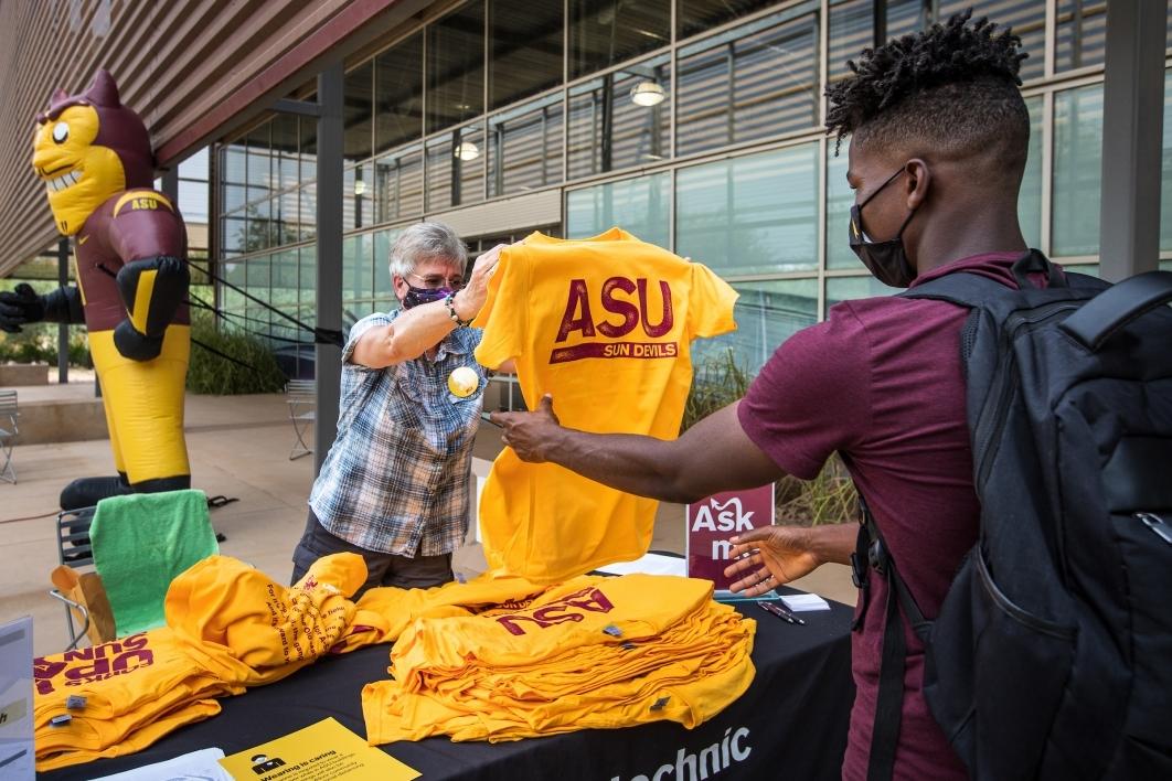 professor handing student an ASU tshirt