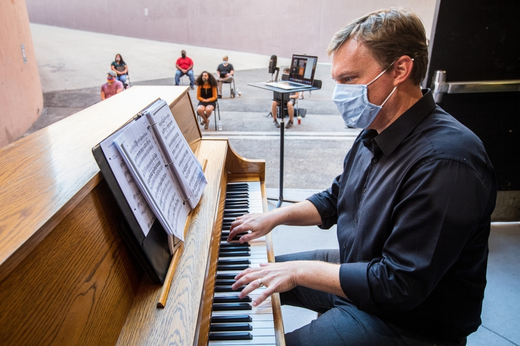 An opera teacher plays an upright piano as his students practice in a loading dock