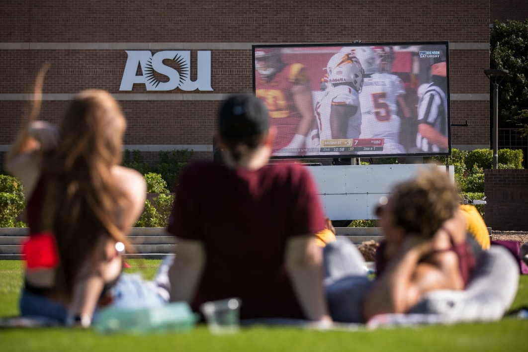 Students watch an ASU football game on a giant TV on the West campus