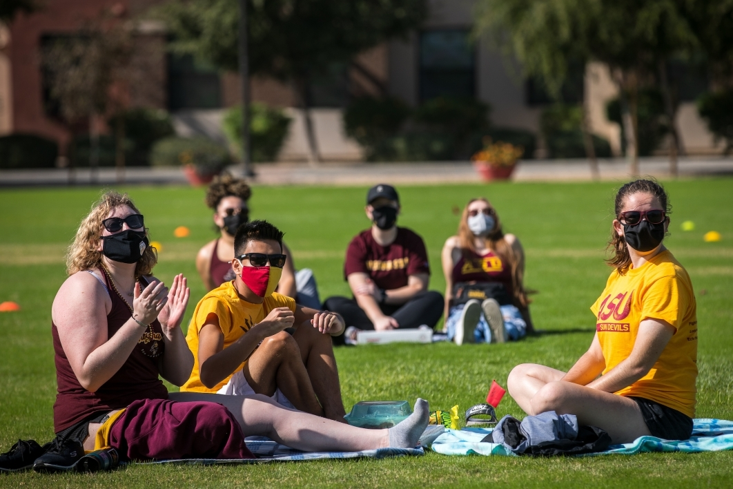 Small groups of students sit spaced out on a field to watch the ASU football game on a giant TV