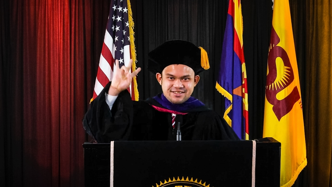 A graduate speaks at a lectern in front of flags