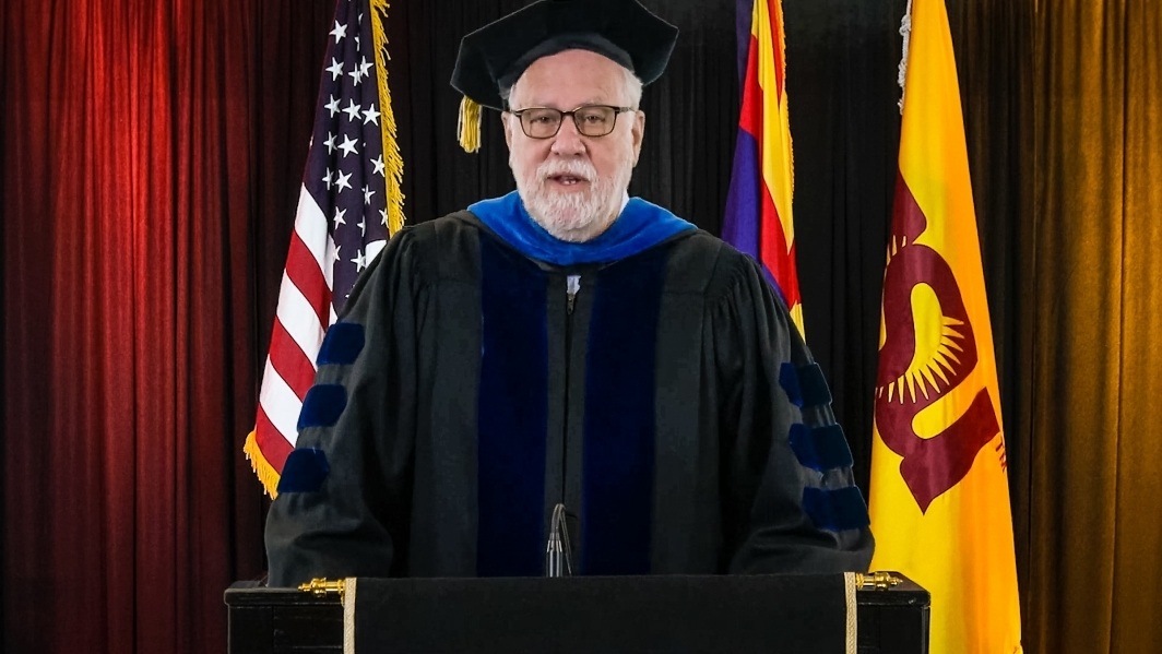 ASU Provost Mark Searle speaks at a lectern in front of flags