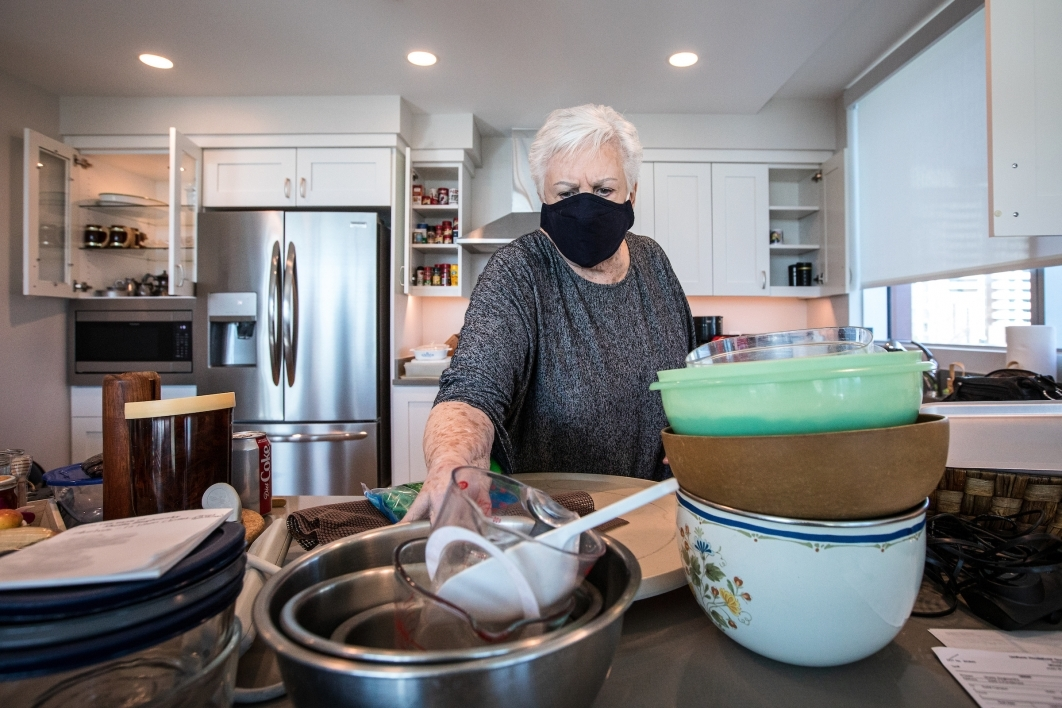 A woman in a mask unpacks dishes and bowls in her new kitchen