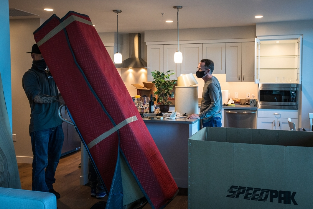 A man moves a tall piece of furniture into a new apartment