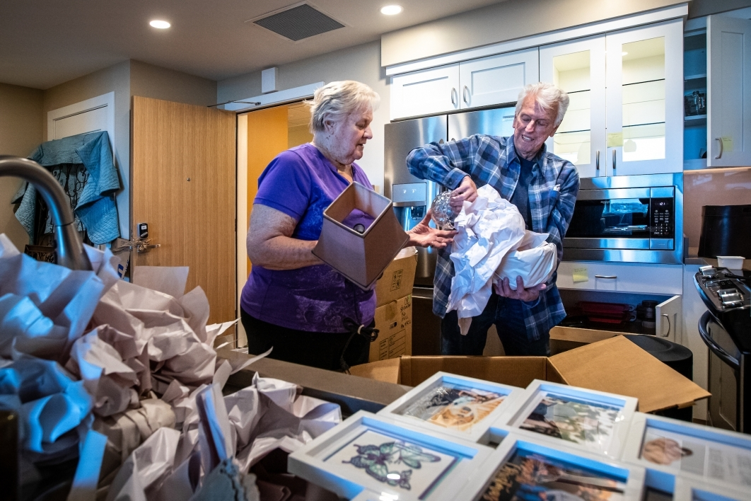 An older couple unpack dishes in their new kitchen