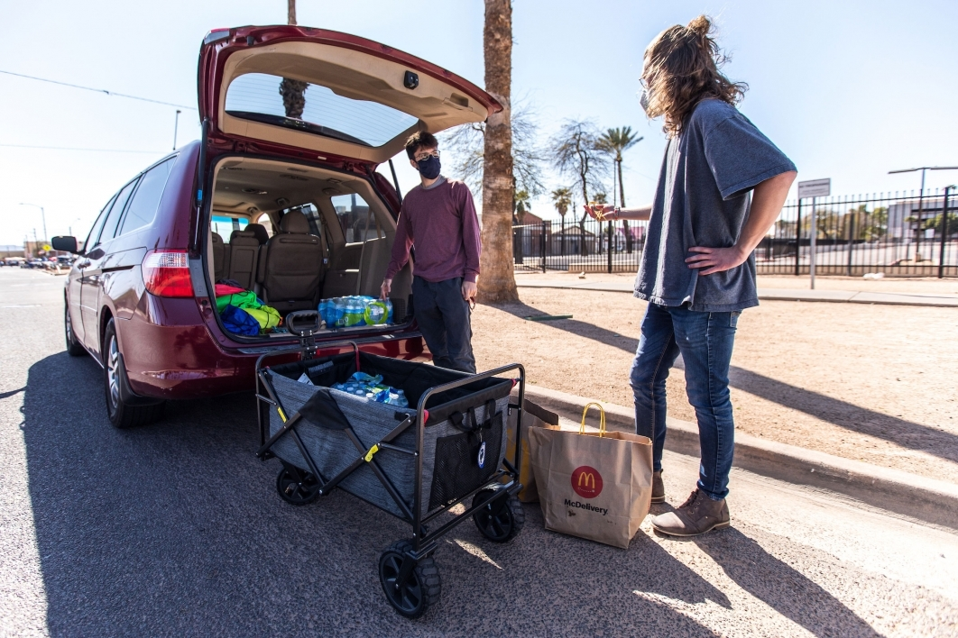 Two young men load food and water into a wagon to distribute to the homeless