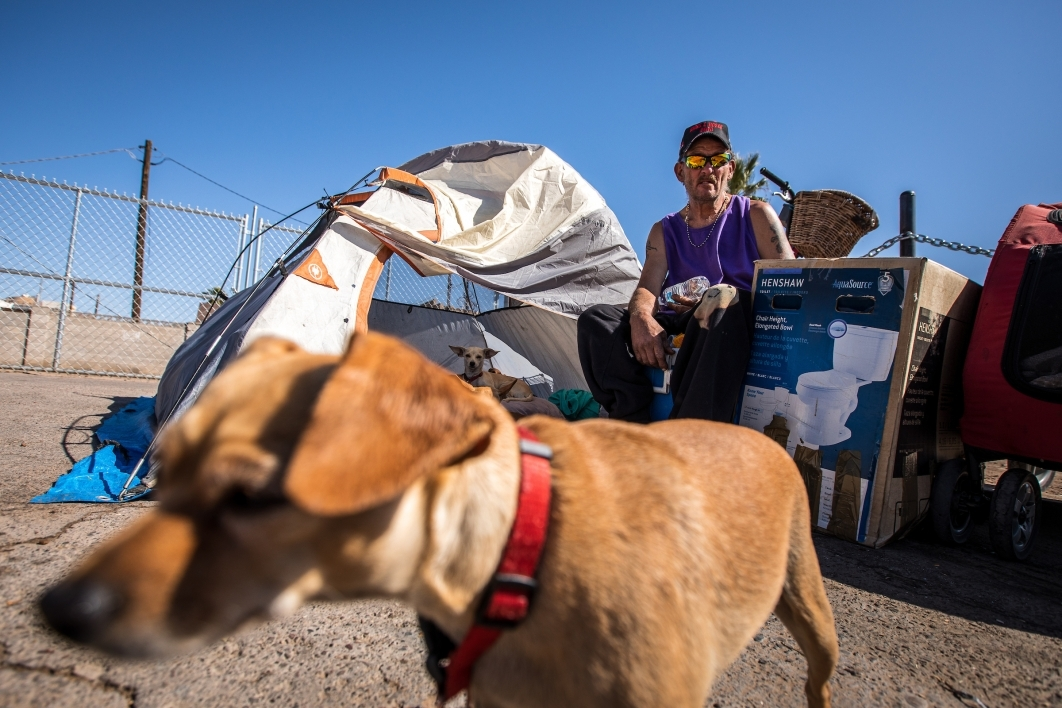 A homeless man sits outside his tent with his five Chihuahuas