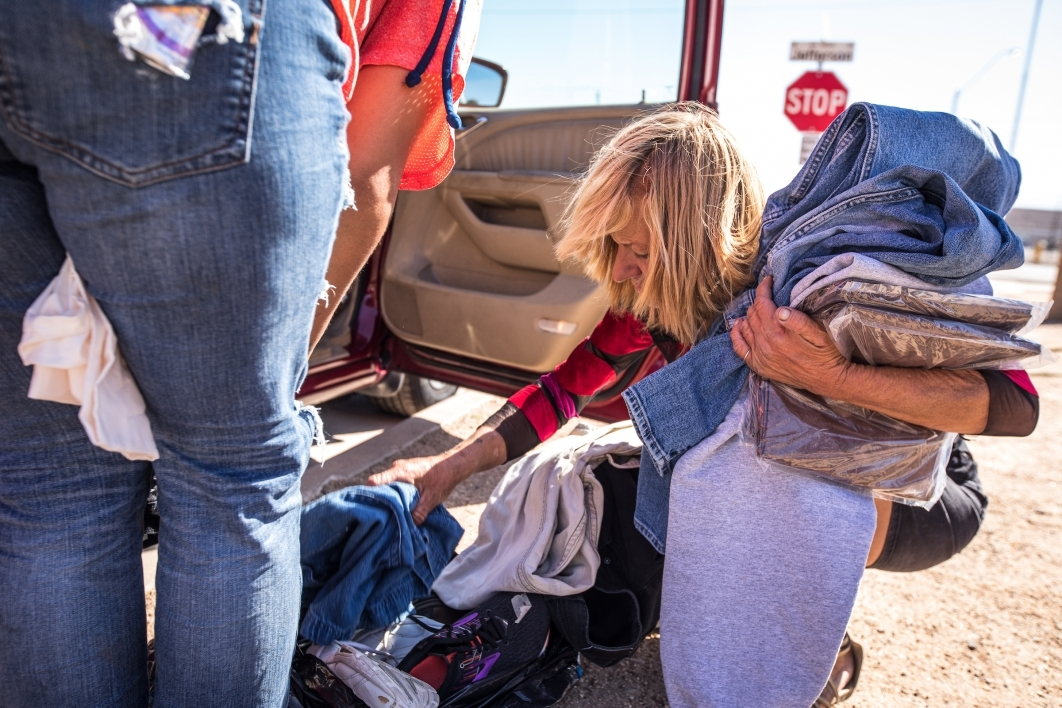 A homeless woman searches through a bag of clothing next to a van