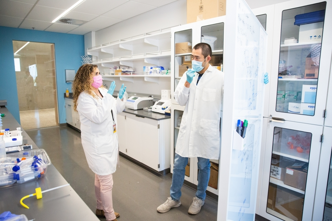 A woman and a man in lab coats discuss items on a white board in a lab