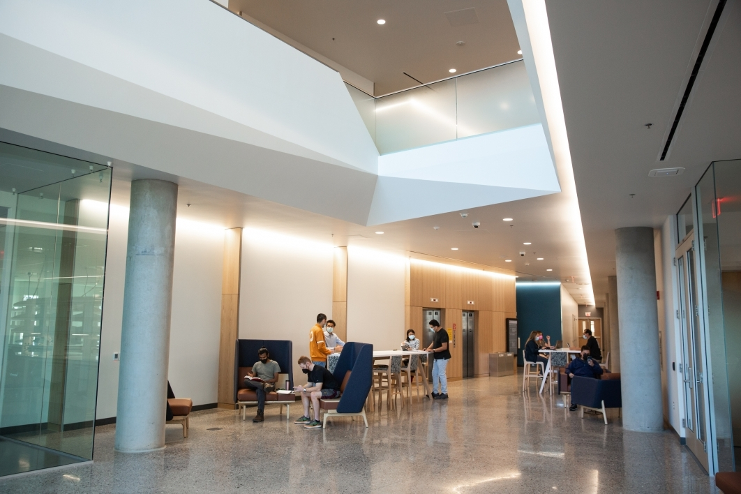 Student researchers work in a breezeway on various tables and lounge chairs