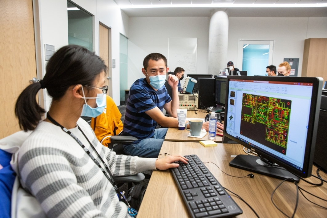 A man and a woman in masks work on computers in a health computing lab