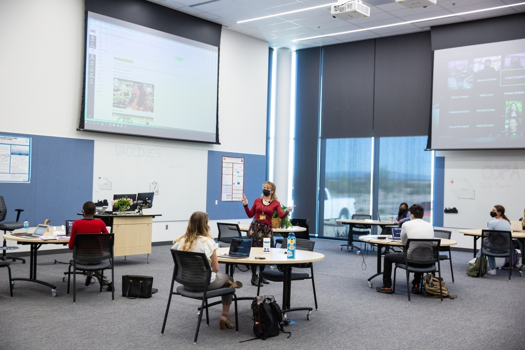 Students sit distanced at tables while a professor leads a class, with large screens showing others on Zoom
