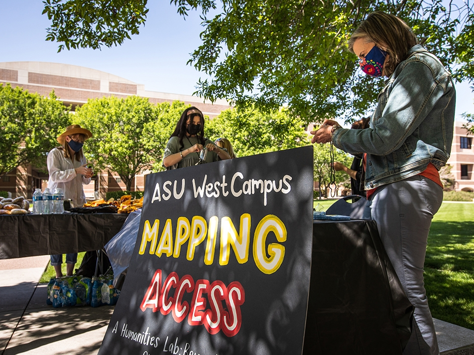 two people at outdoor table that says ASU West Campus Mapping Access