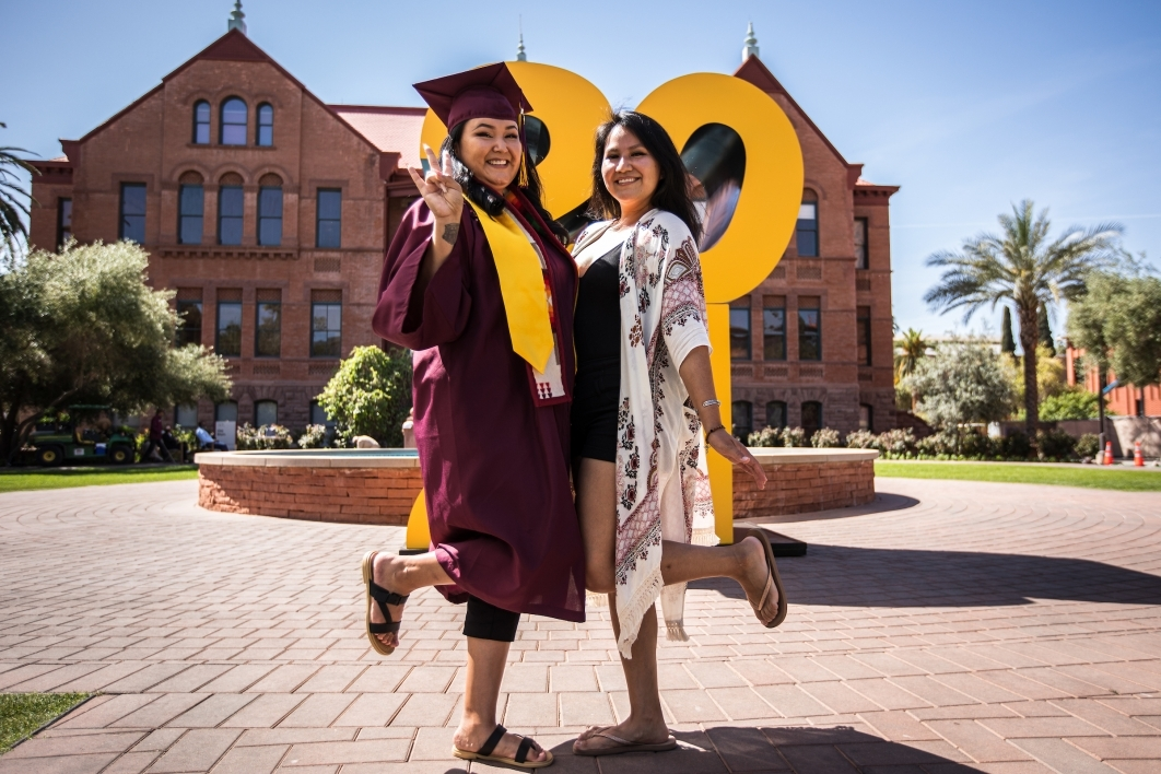 A woman in a graduation cap and gown poses with her sister in front of a giant 2021 sign