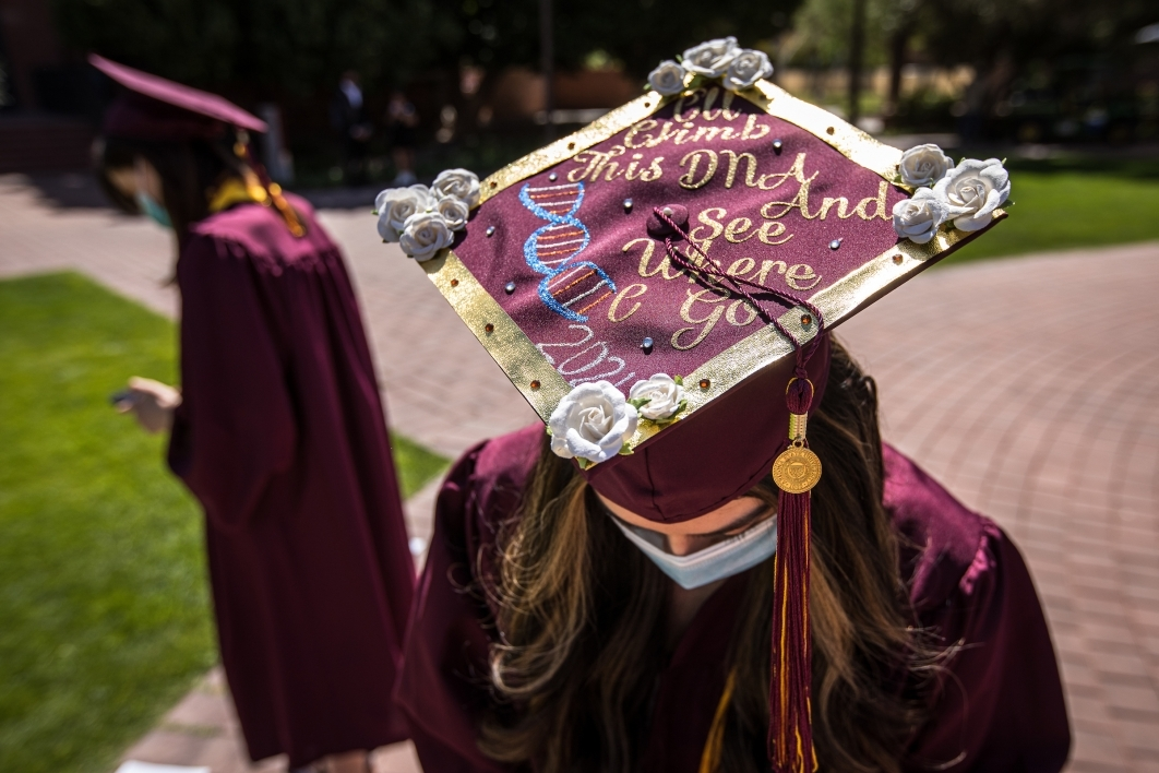A woman tilts her head forward so the wording on her graduation cap can be read: I'll climb this DNA and see where I can go