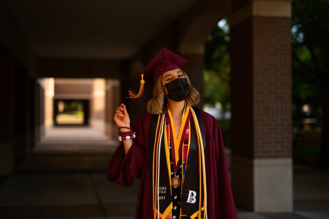 woman wearing a mask and a cap and gown standing in a hallway
